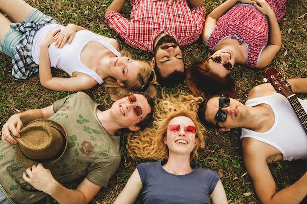 Группа лучших друзей весело вместе, лежа в траве