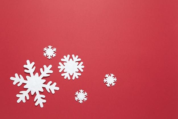 Группа больших и малых белых чувствовал снежинки на бордовый красный, копия пространства.