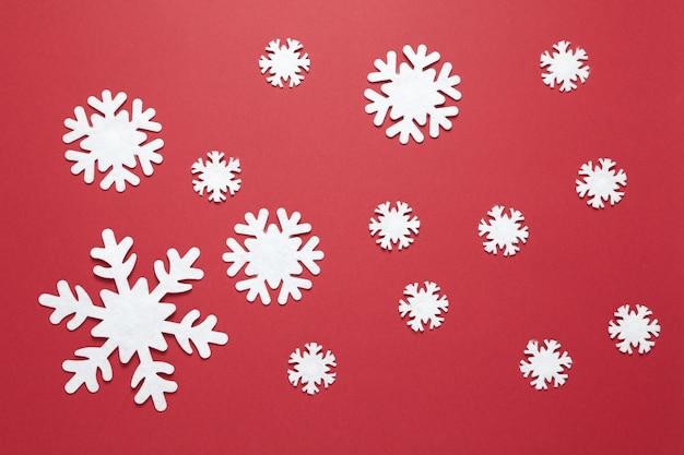Группа больших и маленьких белых войлочных снежинок на бордовый красный.