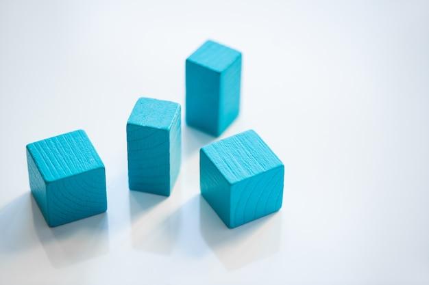 Группа синих плоских деревянных кирпичей и кубиков, стоящих в случайном порядке на белом фоне изолированно