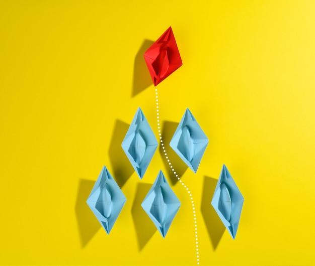Группа синих бумажных корабликов и один красный светодиод на желтом фоне. концепция сильного лидера, рост уникальных и талантливых сотрудников, вид сверху