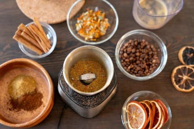 コーヒー豆、ドライフラワー、オレンジスライス、シナモンスティック、砂糖漬けの果物、その他の石鹸を作るための材料が入ったボウルのグループ