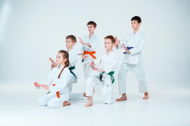 Группа юношей и девушек воюет в айкидо на тренировке в школе боевых искусств. концепция здорового образа жизни и спорта