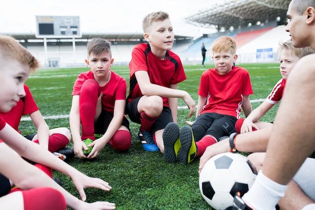 コーチを聞いている男の子のグループ