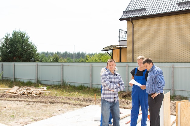 新しい家の基礎にあるクリアされた住宅区画の詳細について話し合っているビルダーとサイトエンジニアのグループ