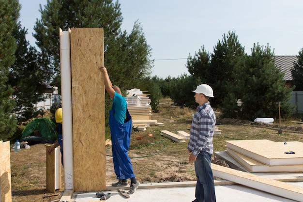주거 지역에 새로 지은 집의 바닥에 단열된 나무 벽 패널을 세우는 건축업자 그룹