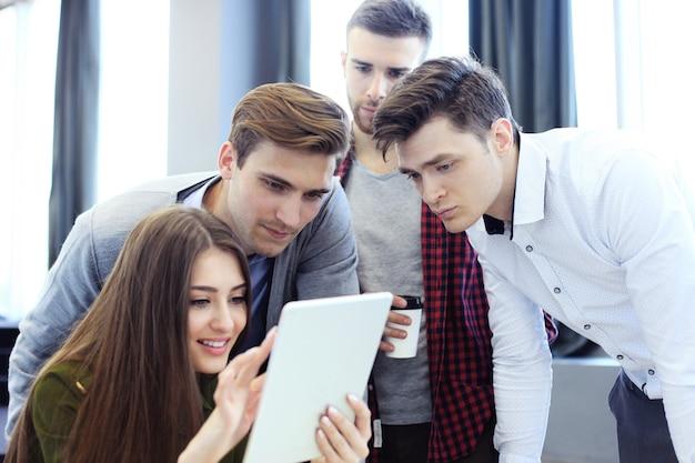 태블릿에서 작업하는 비즈니스 사람들의 그룹입니다.