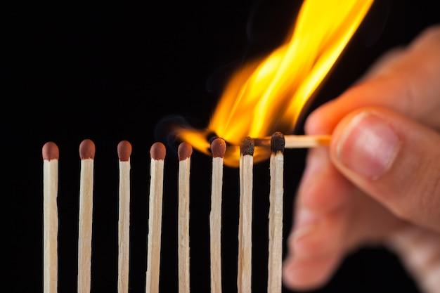 Группа сожженных и несгоревших спичек, изолированных на черном фоне.