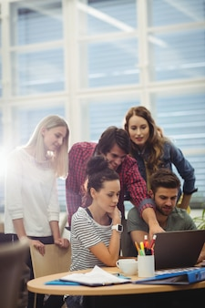 Группа руководителей компаний обсуждают над ноутбуком на их дез
