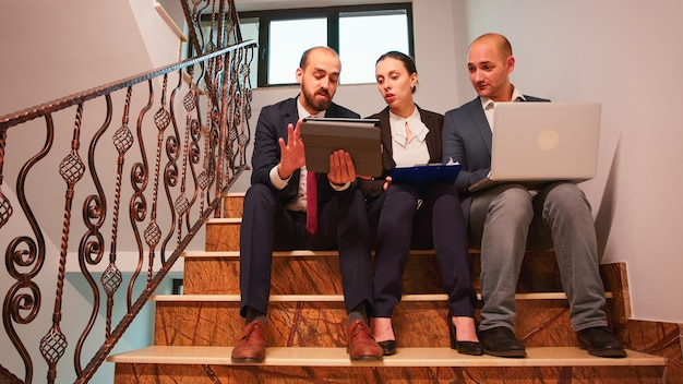 ノートパソコンとタブレットの分析レポートを使用して財務プロジェクトを説明する階段に座って作業の計画を立てるビジネスパートナーのグループ。忙しい階段で会社のマネージャーとオフィスエグゼクティブのチーム。