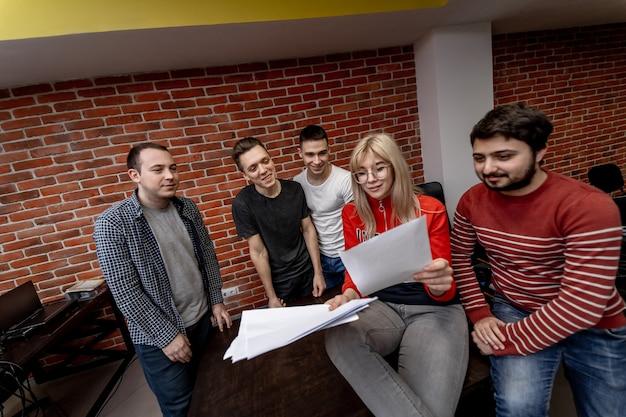 Группа деловых людей и разработчиков программного обеспечения, работающих как одна команда в офисе. веселое сотрудничество, коллеги.