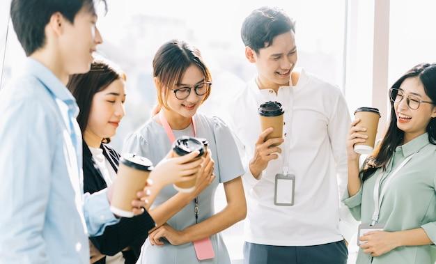 ビジネスマンのグループは休憩中にチャットやコーヒーを飲んでいます