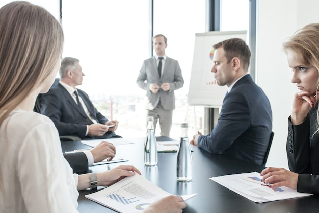 사무실의 플립 차트에서 다이어그램 및 그래프로 보고서 프레젠테이션을 보고 있는 회의에서 비즈니스 사람들 그룹