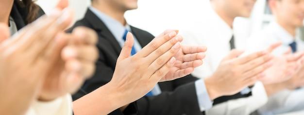会議で彼らの手を叩くビジネス・グループのグループ