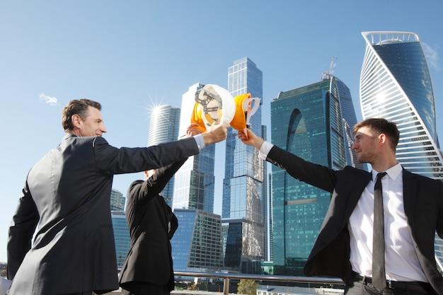 Группа деловых людей, звенящих касками в знак успеха на небоскребах, концепция строительства завершена