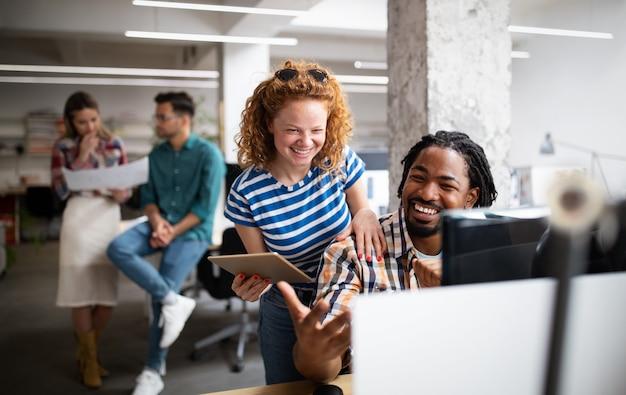 Группа деловых людей, дизайнеров и разработчиков программного обеспечения, работающих как одна команда в офисе.