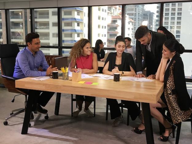 Группа деловых людей обсуждает и сосредоточена на оформлении документов на встрече.