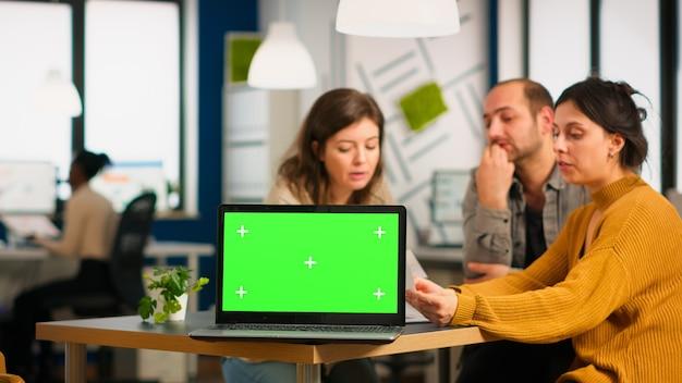 カメラの前にモックアップラップトップ、机の上に置かれた金融プロジェクトのプレゼンテーションの準備ができているpcで会社の計画について話し合っているビジネスマンのグループ。クロマキーディスプレイを備えたグリーンスクリーンpcを使用するリーダー