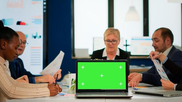 카메라 앞에 모의 노트북으로 회사 계획을 논의하는 기업인 그룹, 책상 위에 놓인 재무 프로젝트 프레젠테이션 준비가 된 pc. 크로마 키 디스플레이가 있는 녹색 화면 pc를 사용하는 리더