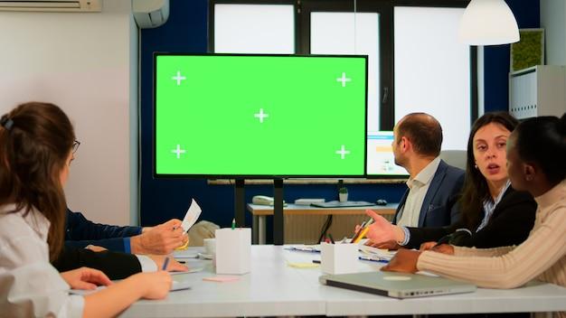 机の前にモックアップテレビの緑色の画面で会社の計画について話し合っているビジネスマンのグループ。財務プロジェクトのプレゼンテーションの準備ができています。クロマキーディスプレイ付きのモックアップモニターを使用する多民族チーム