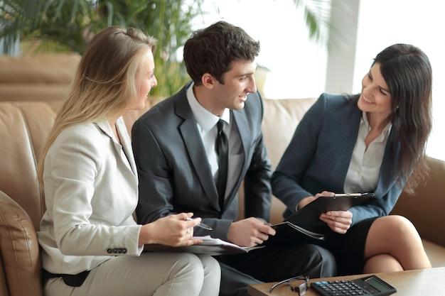 銀行ホールでドキュメントを議論するビジネスマンのグループ。ビジネスコンセプト