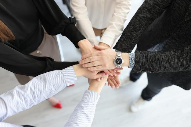Группа деловых людей, складывающих много рук крупным планом