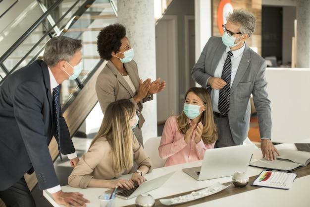 ビジネス人々のグループは会議を持ち、オフィスで働いており、コロナウイルスからの保護としてマスクを着用しています