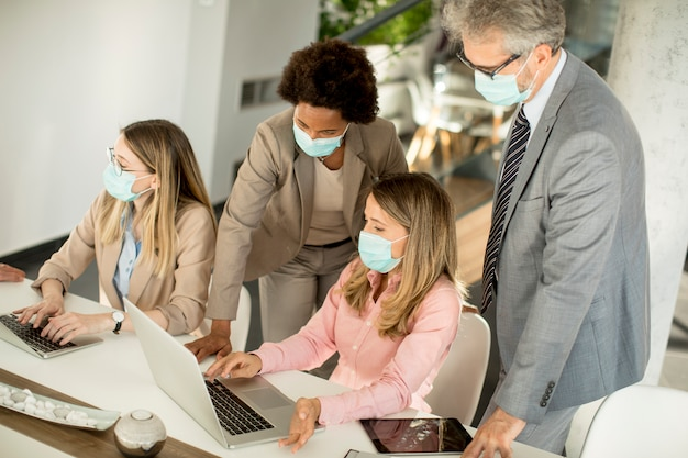 ビジネスの人々のグループが会議を持ち、オフィスで働いており、コロナウイルスからの保護としてマスクを着用しています