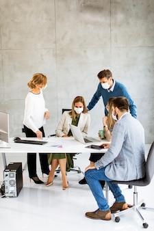 Группа деловых людей встречается и работает в офисе и надевает маски в качестве защиты от вируса короны.