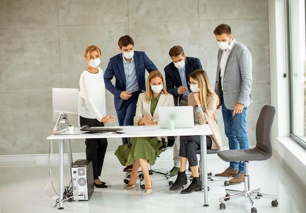ビジネスマンのグループは、オフィスで会議と作業を行い、コロナウイルスからの保護としてマスクを着用します