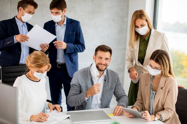 ビジネスマンのグループは、オフィスで会議や作業を行い、コロナウイルスからの保護としてマスクを着用します