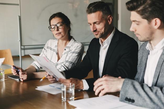 オフィスのテーブルに座って、就職の面接-ビジネス、キャリア、配置の概念の間に新人の履歴書を調べるフォーマルなスーツのビジネス人々のグループ