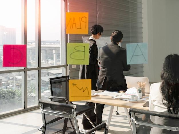 Группа деловых людей в элегантной официальной одежде, проводящая встречу за стеклянной доской в современном офисе, вместе обсуждая план идеи бизнес-цели