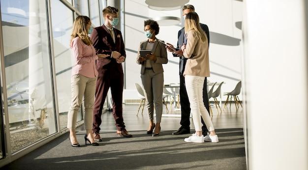 コロナウイルスによる感染を防ぐためにオフィスで会って働いているビジネスマンのグループとマスクを着用してください