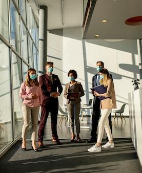 コロナウイルスによる感染を防ぐためにオフィスで会って働いているビジネスマンのグループと保護のためのマスクを着用してください
