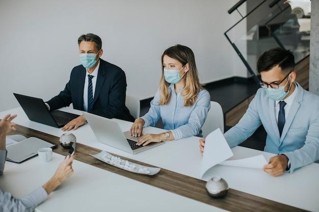 Группа деловых людей на встрече в современном ярком офисном интерьере