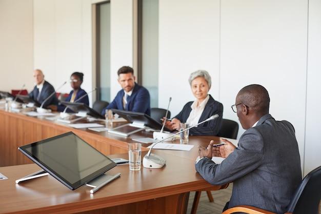 テーブルに座って、役員室でのビジネス会議中にスピーカーを聞いているビジネスマンのグループ