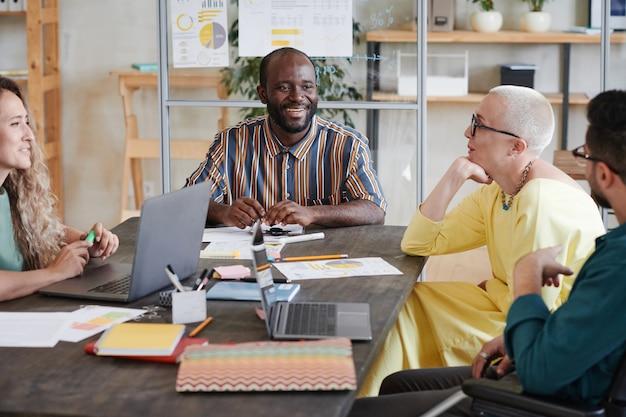 Группа деловых людей, сидящих за столом и вместе планирующих новую бизнес-стратегию на деловой встрече в офисе