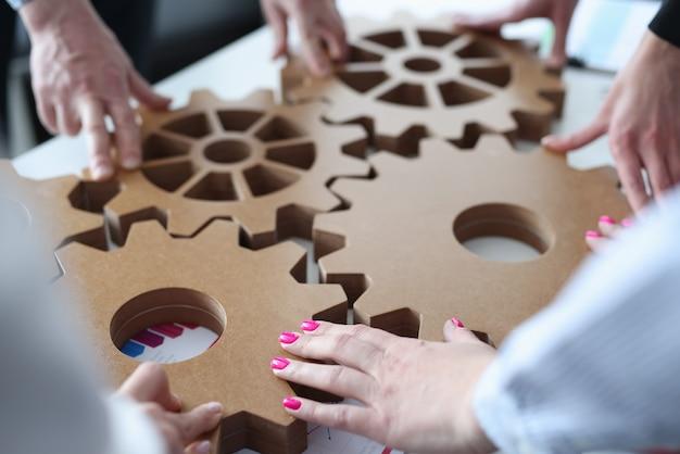 Группа деловых людей, штабелирующих деревянные шестерни крупным планом
