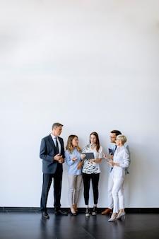 Группа деловых людей, стоящих у стены в офисе