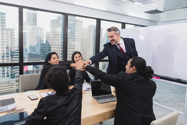 ビジネスの人々のチームのグループの成功を祝って勝利の結束を獲得