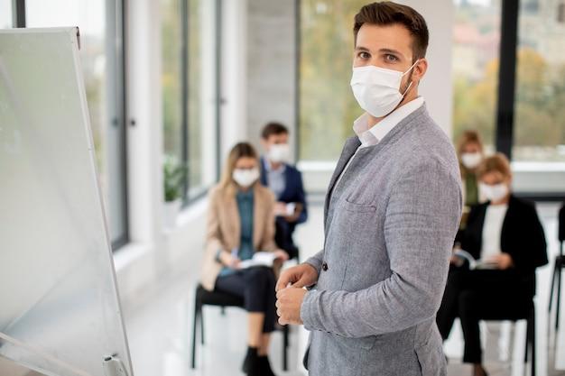 企業の教育フォーラムビジネスセミナーで保護フェイシャルマスクを持つビジネスマンのグループ