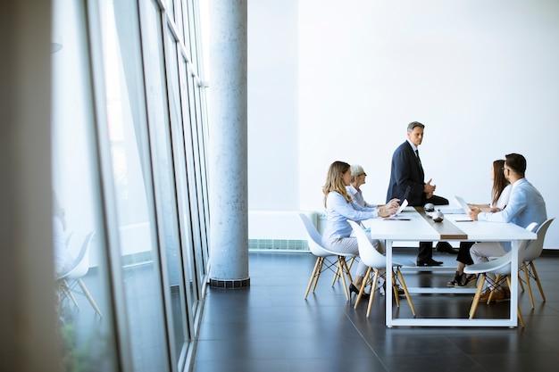 Группа деловых людей с молодыми людьми и старшим коллегой женщины на встрече в современном ярком интерьере офиса
