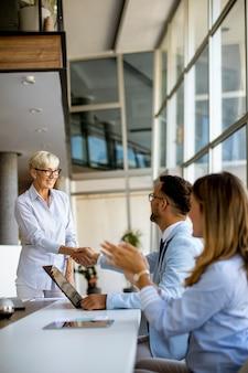 현대 밝은 사무실 인테리어에서 회의에 젊은 성인과 수석 여자 동료와 함께 사업 사람들의 그룹