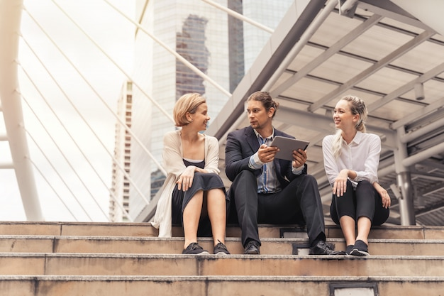 働くと彼の成熟した同僚と何か肯定的なことを話し合って、首都の屋外でタブレットを使用するビジネス人々のグループ