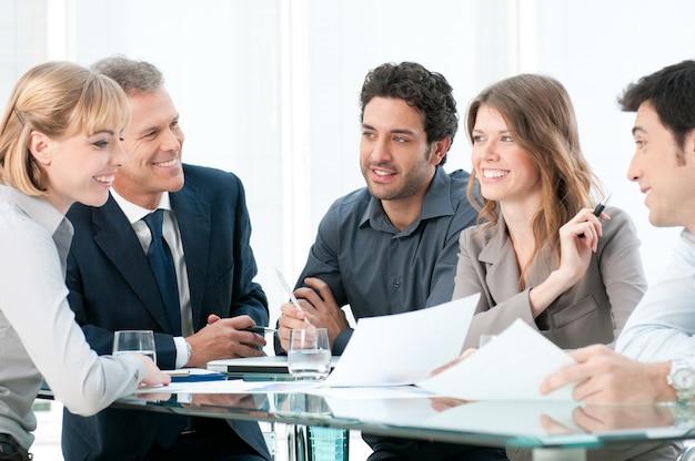 働くとオフィスで一緒に議論するビジネス人々のグループ