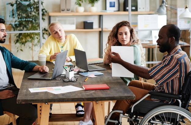 Группа деловых людей, работающих в команде, они сидят за столом с компьютерами и разговаривают друг с другом во время встречи в офисе