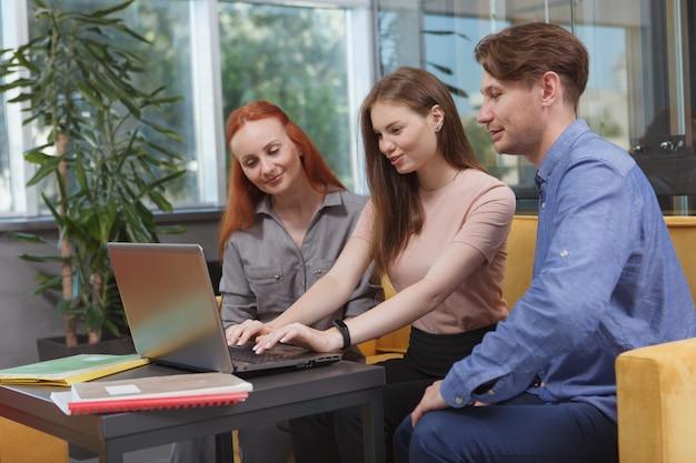 현대 사무실에서 함께 노트북에서 일하는 사업 사람들의 그룹