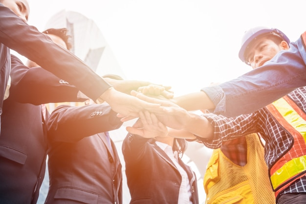 エンジニアとビジネスパーソンのグループは、プロジェクトを成功させるための手の調整です。チームワークの概念