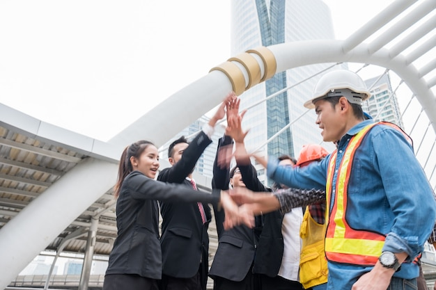 手でエンジニアリングパートナーシップを持つビジネスパーソンのグループは、成功のお祝いを上げました